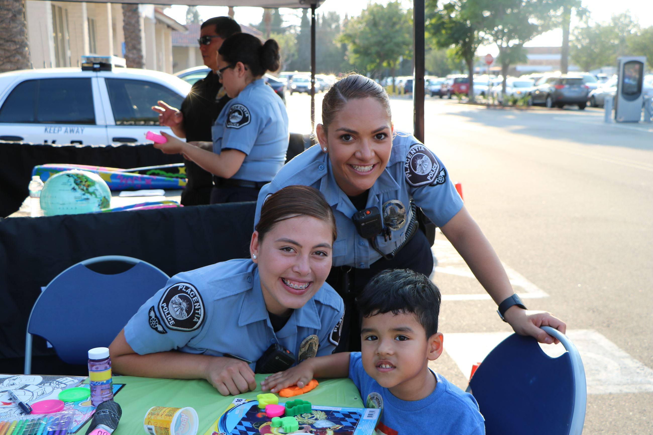 Two Placentia Cadets posing with child at City event